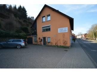 Buitenland woon/bedrijfspand, parkeerplaats tuin, terras en 2 garages